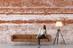 Vrouw in baksteenwoonkamer Stock Fotografie