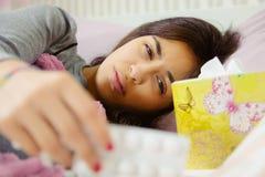 Vrouw in bed die geneeskunde nemen die ziek voelen Royalty-vrije Stock Foto