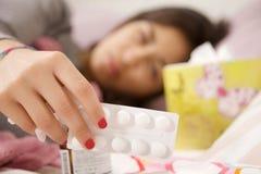 Vrouw in bed die geneeskundenadruk op pillen nemen Stock Afbeelding