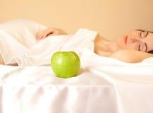Vrouw in bed met appel (nadruk op appel) Stock Foto