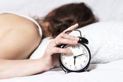 Vrouw in beddraaien van alarm in de ochtend de vrouw wil niet vroeg ontwaken het meisje sliep niet goed De grote klok verzekert o stock afbeelding