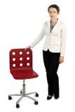 Vrouw in bedrijfskleding die zich dichtbij rode leunstoel bevindt Stock Foto's