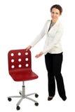Vrouw in bedrijfskleding die zich dichtbij rode leunstoel bevindt Royalty-vrije Stock Afbeelding