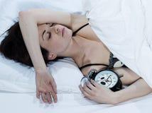 Vrouw in bedslaap met een wekker Stock Fotografie