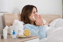 Vrouw Besmet met Koude die op Bed liggen stock foto