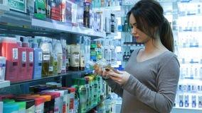 Vrouw bij apotheek het kopen shampoo stock videobeelden