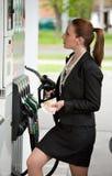 Vrouw bij benzinestation Stock Foto's