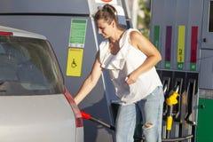 Vrouw bij benzinestation Het meisje giet brandstof in de tank van de machine bij de brandstofpost stock afbeelding