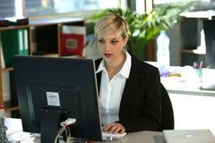 Vrouw bij bureau dat computer met behulp van Stock Afbeelding