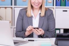 Vrouw bij bureau het typen en het overseinen met haar mobiele telefoon royalty-vrije stock foto's