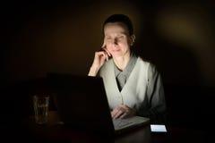 Vrouw bij Computer in Dark Stock Foto's