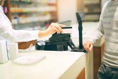Vrouw bij de apotheek kopende geneesmiddelen stock afbeeldingen