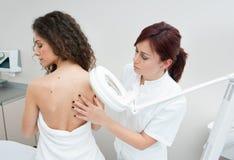 Vrouw bij de dermatologieonderzoek