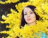 Vrouw bij de gele Forsythia stock afbeeldingen