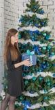 Vrouw bij de Kerstboom die met blauwe ballen wordt verfraaid Stock Foto