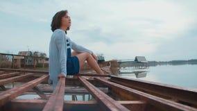 Vrouw bij de pijler door de rivier stock footage