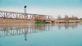 Vrouw bij de pijler door de rivier stock video