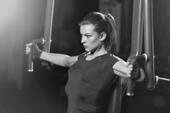 Vrouw bij de sportgymnastiek die wapensoefeningen op een machine doen Royalty-vrije Stock Afbeelding