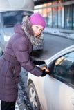 Vrouw bij de winter schoonmakende autoramen Royalty-vrije Stock Foto's