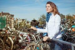 Vrouw bij een fietsparkeren in Amsterdam Stock Fotografie