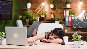 Vrouw bij haar werkplaatsslaap terwijl haar collega werkt stock footage