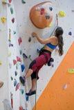 Vrouw bij het beklimmen van muur stock afbeelding