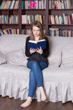 Vrouw bij het boek van de bibliotheeklezing Royalty-vrije Stock Foto's