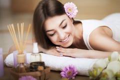 Vrouw bij het KUUROORD Gezond levensstijl en ontspanningsconcept Een mooie jonge vrouw op een massagelijst Aromaolie en boter Kuu Royalty-vrije Stock Foto's