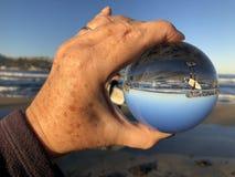 Vrouw bij het strand die een kristallen bol houden stock foto