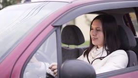 Vrouw bij het wiel in haar nieuwe auto stock videobeelden