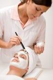Vrouw bij kuuroord dat gezichtsmasker krijgt Royalty-vrije Stock Afbeeldingen