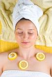 Vrouw bij kuuroord met citroen op huid Stock Afbeelding