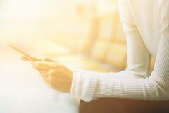 Vrouw bij luchthaven het texting op een smartphone stock afbeeldingen
