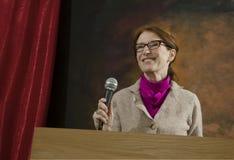 Vrouw bij podium met microfoon stock foto