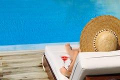 Vrouw bij poolside met kosmopolitische cocktail Royalty-vrije Stock Foto's