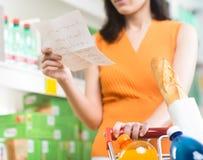 Vrouw bij supermarkt met het winkelen lijst Stock Foto's