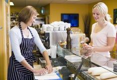 Vrouw bij teller in restaurant dienende klant stock afbeeldingen