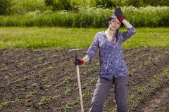 Vrouw bij tuin wordt vermoeid die Royalty-vrije Stock Foto