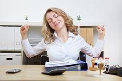 Vrouw bij zich bureau het uitrekken Stock Fotografie