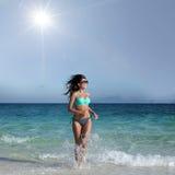 Vrouw in bikini aan strand in werking dat wordt gesteld dat Stock Afbeeldingen