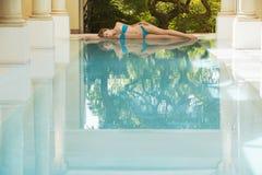 Vrouw in Bikini die door Zwembad liggen Royalty-vrije Stock Fotografie