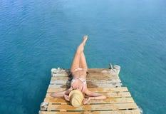Vrouw in bikini die op het dok liggen stock afbeelding