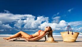 Vrouw in bikini die op strand in Seychellen liggen Royalty-vrije Stock Afbeelding