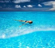 Vrouw in bikini die op water liggen Stock Fotografie