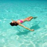 Vrouw in bikini die op water ligt Stock Foto's