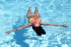 Vrouw in bikini die in zwembad drijft royalty-vrije stock afbeeldingen