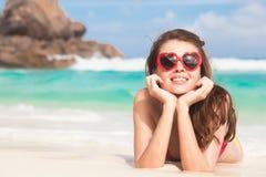 Vrouw in bikini en hart gevormde zonnebril die op tropisch strand liggen royalty-vrije stock foto