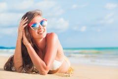 Vrouw in bikini en rode zonnebril die op tropisch strand liggen stock afbeeldingen