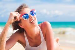 Vrouw in bikini en rode zonnebril die op tropisch strand liggen royalty-vrije stock afbeeldingen