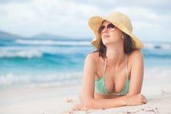 Vrouw in bikini en strohoed die genietend van zonnige dag op tropisch strand liggen royalty-vrije stock foto